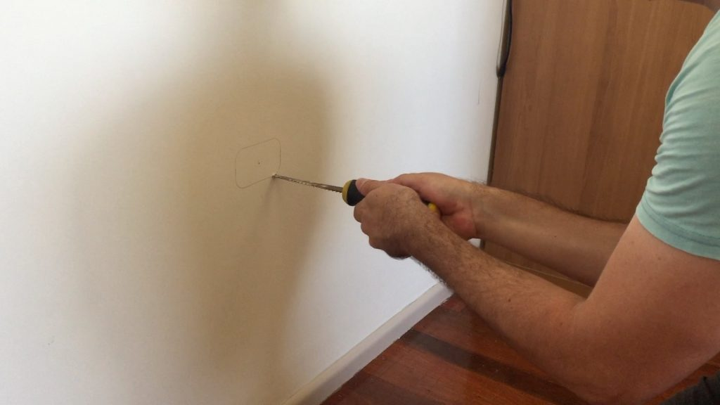 Cutting the hole with a plasterboard jab saw